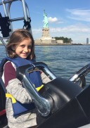 Girl driving boat by the Statue of Liberty